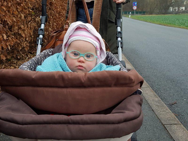Ronja guckt aus dem Kinderwagen