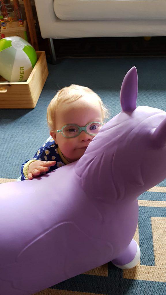 Bild: Baby mit Down Syndrom mit Einhorn