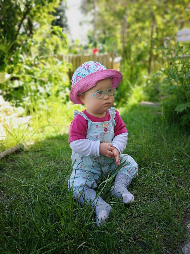 Bild: Baby mit Down Syndrom im Garten