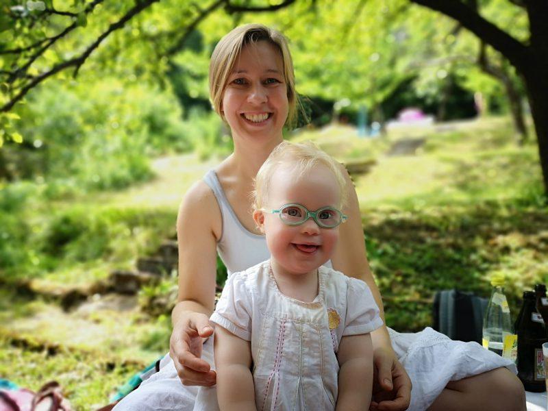 Kleinkind mit Down Syndrom mit Mama im Grünen