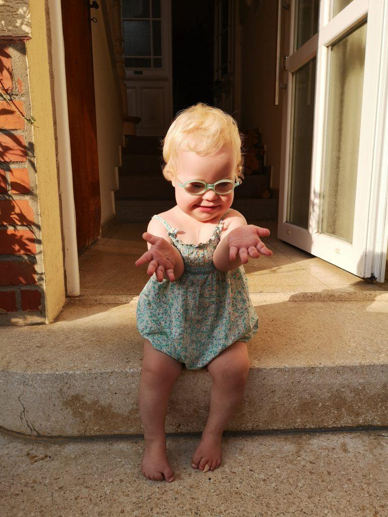 Kind mit Down Syndrom sitzt auf Treppe
