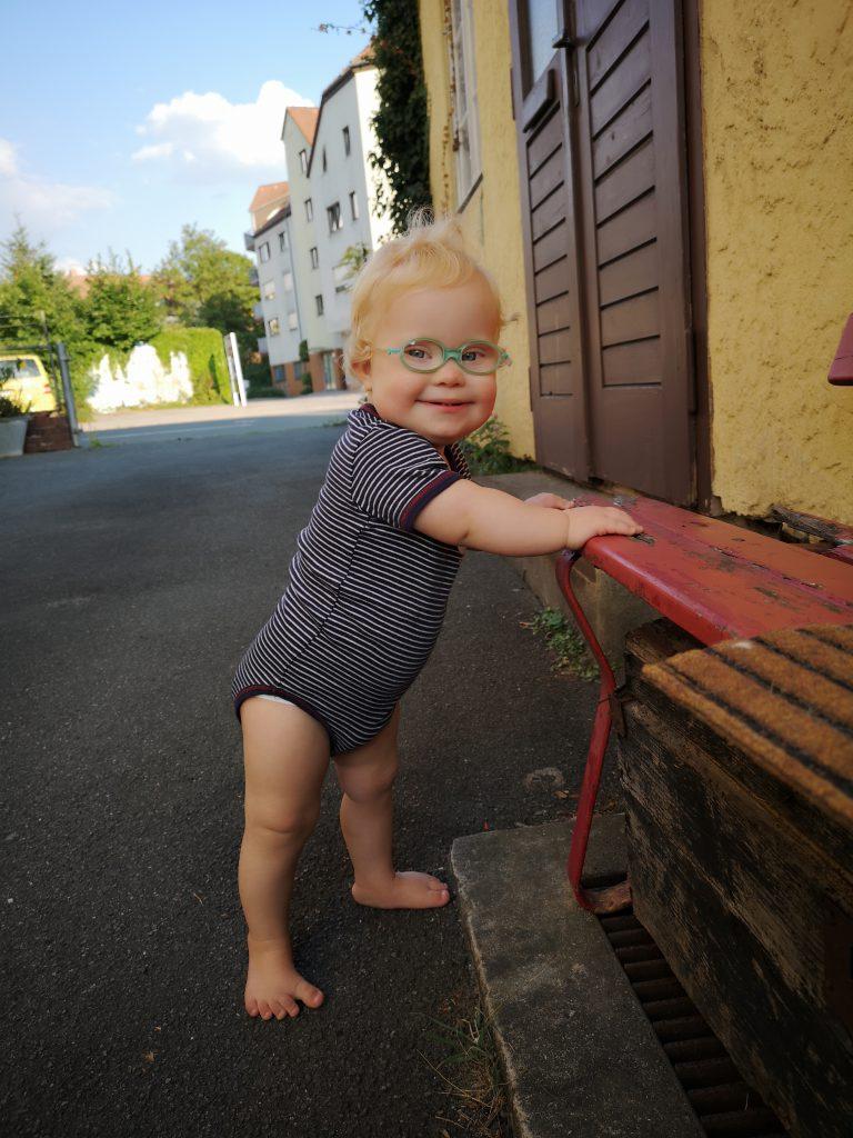 Kleinkind mit Down Syndrom steht