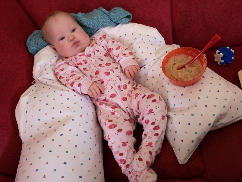 Baby mit Down Syndrom isst Brei