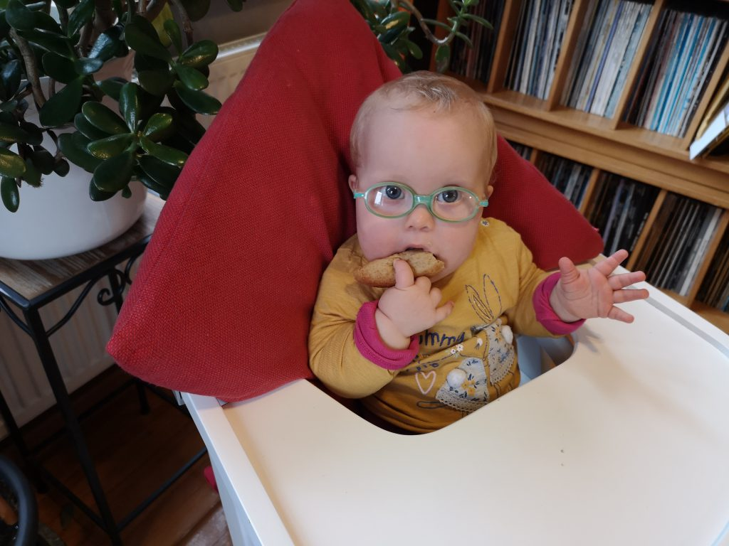 Baby mit Down Syndrom isst Brot