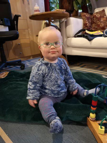 Baby mit Down Syndrom sitzt