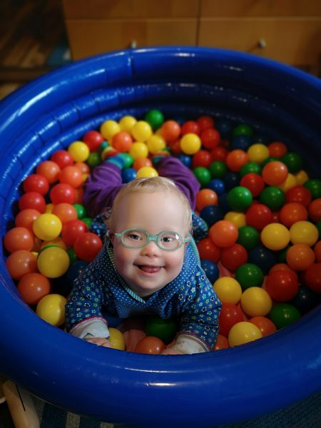 Baby mit Down Syndrom im Bällebad