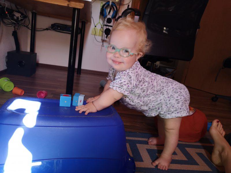 Baby mit Down Syndrom steht