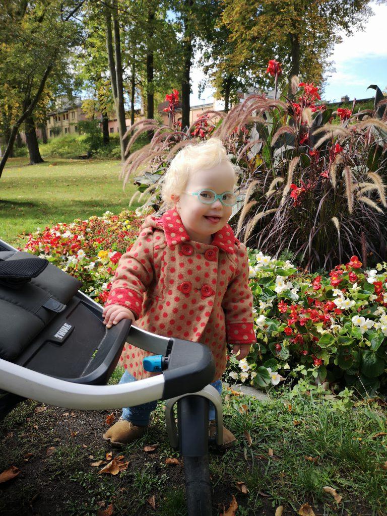 Baby mit Down Syndrom im Garten