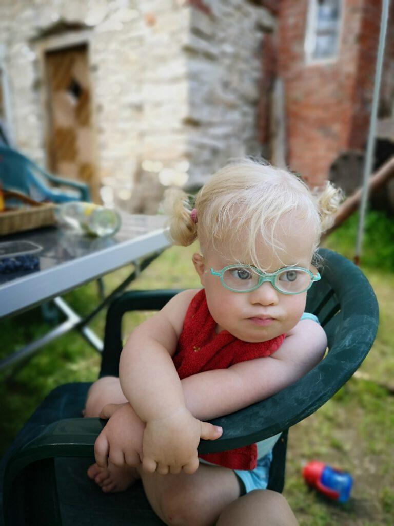 Kleinkind mit Down Syndrom sitzt im Stuhl