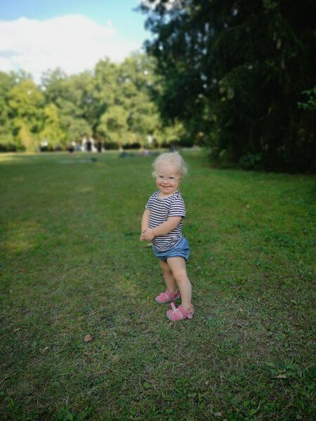 Kleines Mädchen mit Down Syndrom steht im Park