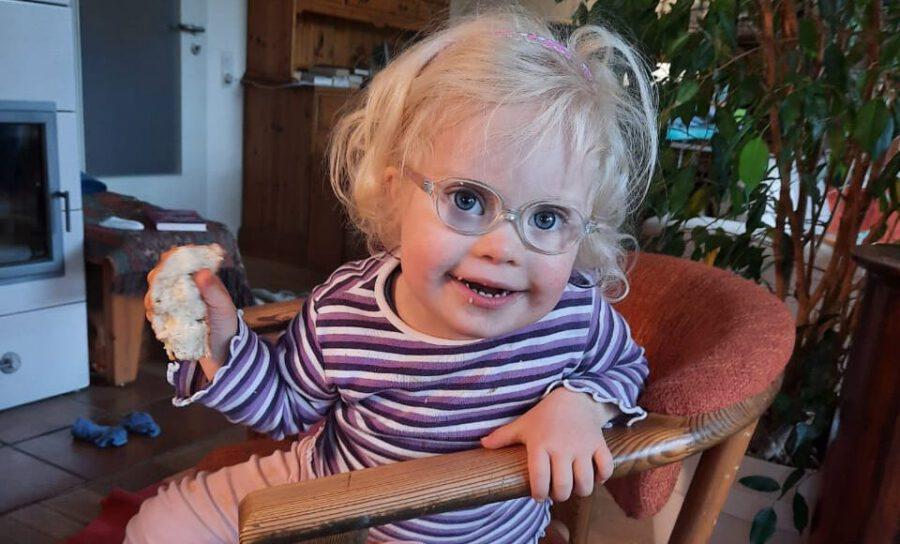 Ronja sitzt auf einem Stuhl und lacht